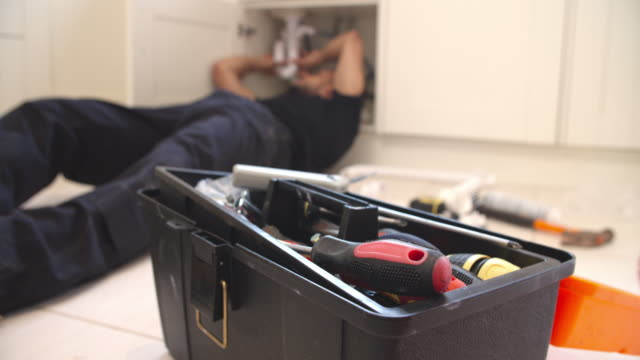 Plumber fixing sink in kitchen, focus on toolbox video