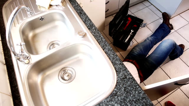 Plumber fixing the sink in a kitchen video
