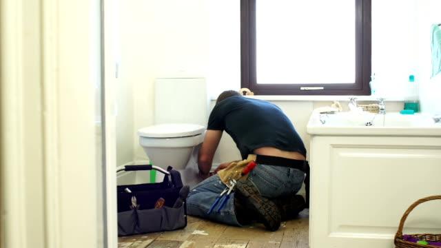 HD DOLLY: Plumber / Handyman fixing the Toilet in Bathroom video