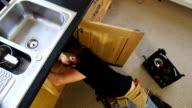 Plumber / Handyman working under Kitchen sink - CRANE HD video