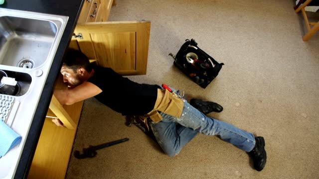 Plumber / Handyman working under Kitchen sink HD video