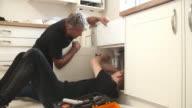 Plumber teaching apprentice to fix kitchen sink video
