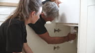 Plumber teaching female apprentice to fit a sink, close-up video