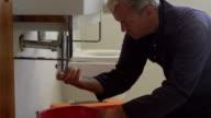 Plumber Working On Sink In Bathroom Shot On R3D video