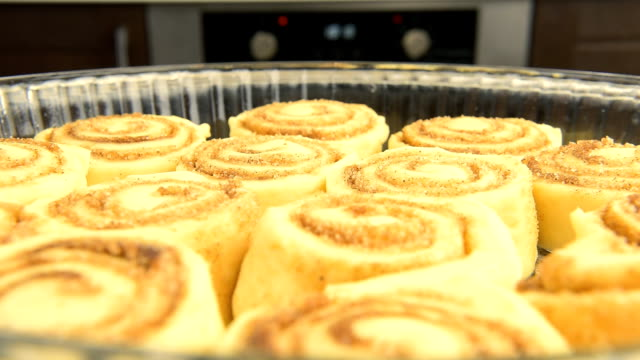 Point of view: cinnamon rolls being put into the hot oven. video