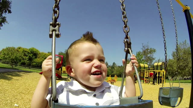 Point of View Happy Baby Boy On Swing At Park video