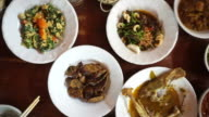 Point of view of hand eating variety traditional Thai food cuisine from top. sticky rice, curry and paste POV video