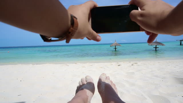 Point of View of Hand taking photo with smart phone. feet and ocean vacation background video