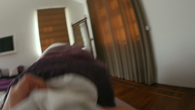 Point of view of man getting up and opening curtains video