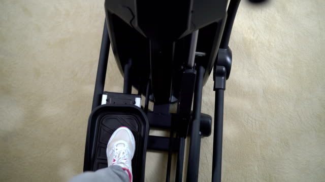 Point of view of woman exercising on elliptical trainer at home video
