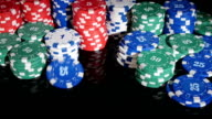 poker chips rolled into the casino on a black background. video