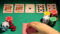Poker player catching full house hand, checking cards before betting video