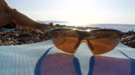 Polarized sports cycling sunglasses on wild beach in summer video