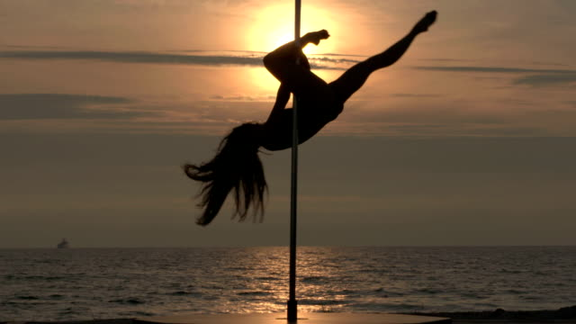 Pole dance fitness exercise on the beach at sunset. video