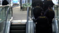 Police officers on moving escalator. Patrol providing safety at railway station video