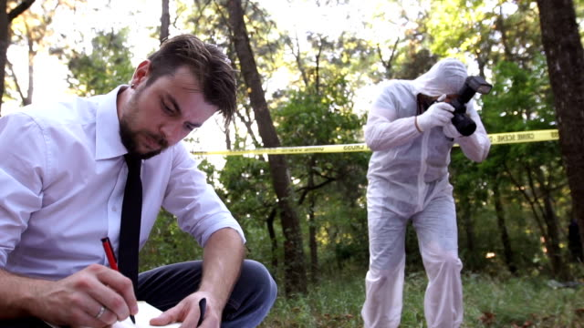 Police taking notes at murder scene video