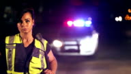 Policewoman in front of car with emergency lights video
