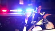 Policewoman standing next to police car, lights flashing video
