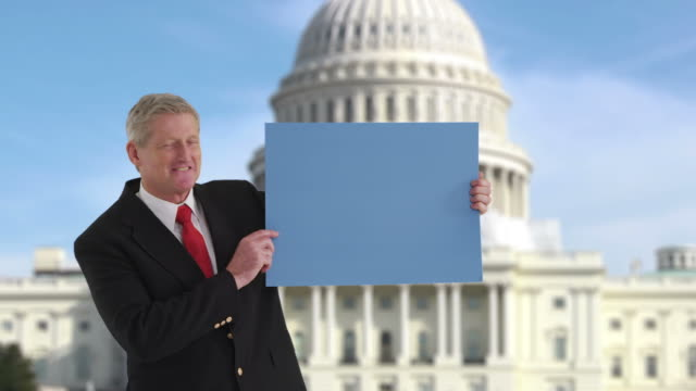 Politician holding sign in front of US Capitol video