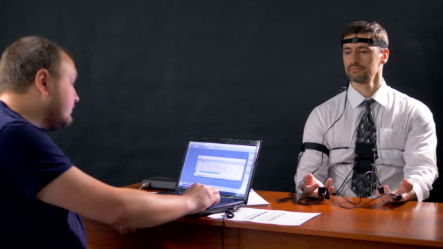 A polygraph technician reads questions from a laptop. video