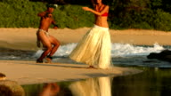 Polynesian dancers perform at beach in Hawaii, slow motion video