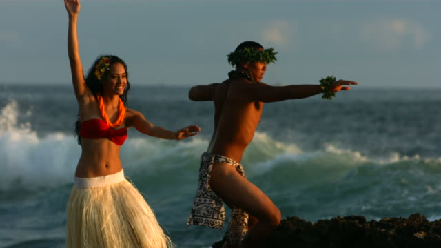 Polynesian dancers perform by ocean, slow motion video