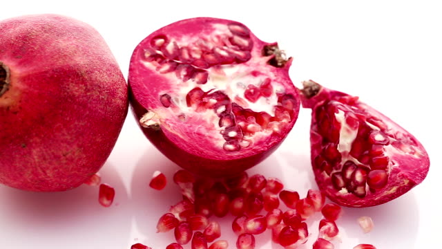 Pomegranate and seeds on white background video