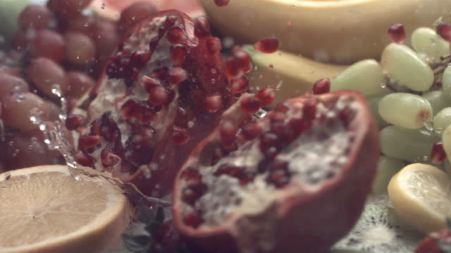 Pomegranate splashing into water, slow motion video