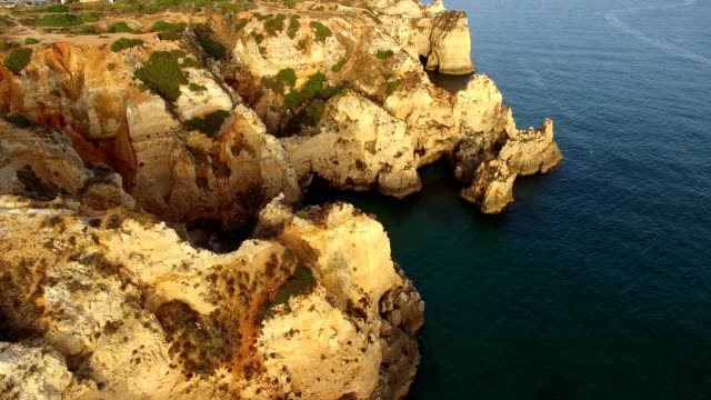 Ponta da Piedade lighthouse on cliff near ocean at sunset, Lagos, aerial view video