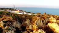 Ponta da Piedade lighthouse on cliff near ocean at sunset, Lagos, aerial view video