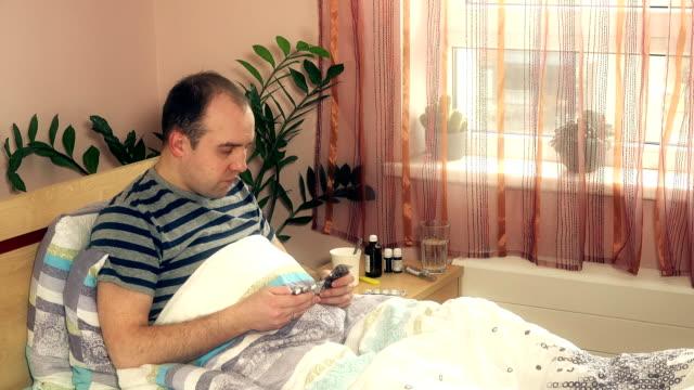Poor sick man guy choosing pills for treatment in his bedroom video