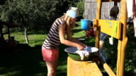Poor villager woman washing clothes by hand in metal bowl in farm yard video