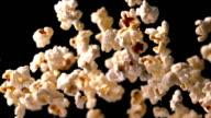 Popcorn bouncing against black background video