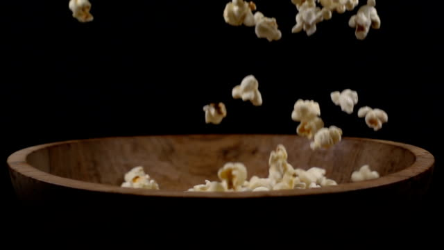 Popcorn falls into a wooden bowl video