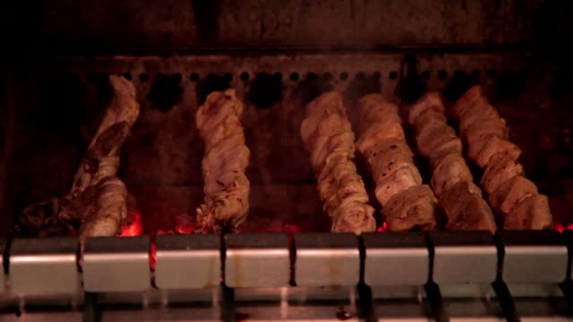Pork meat is cooked on skewers in oven indoors video