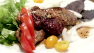 Pork steak with cherry tomatoes and herbs on a white plate video
