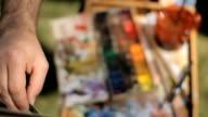 Portable easel. Artist en plein air. Artist working on painting video