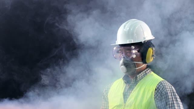 Portrait Asian worker wearing safety protective gear, goggle, mask, hat, vest in danger smoke dark room video