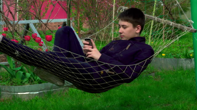 4K Portrait boy Playing Tablet in Hammock, the young man Face Use Smart Phone in Nature video