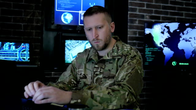 portrait commander male in shape, in monitoring room, military control and security service, safety system tracking terrorists video