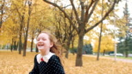 portrait cute little girl with curly hair, in dress with polka dots runing through the autumn alley in the park slow mo video