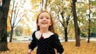 portrait cute little girl with curly hair, in dress with polka dots laugh, jump, have fun in the autumn park slow mo video