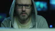 Portrait footage of concentrated male employee wearing a hood and working on a computer in a dark office room with display screens with maps and data. video