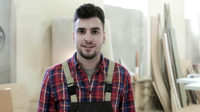 4K Portrait happy joineryworkman or carpenter in checkered shirt and apron. video