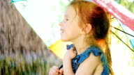 Portrait in profile of a carefree girl who enjoys the rain. It should be under the umbrella of the rainbow color video