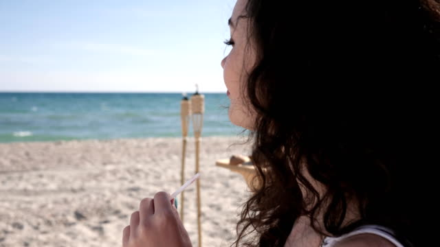 portrait lovely girl with curly hair, drinks cocktail straw, сoconut, summer season, on background sea ocean and sand video