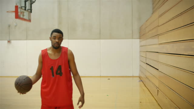Portrait of a basketball player dribbling and spinning a ball by bleachers video