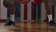 Portrait of a basketball player dribbling between his legs on the court, pan up video