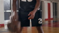 Portrait of a basketball player dribbling intensely on the court, pan up video