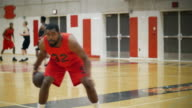 Portrait of a basketball player dribbling the ball with a team playing behind him video
